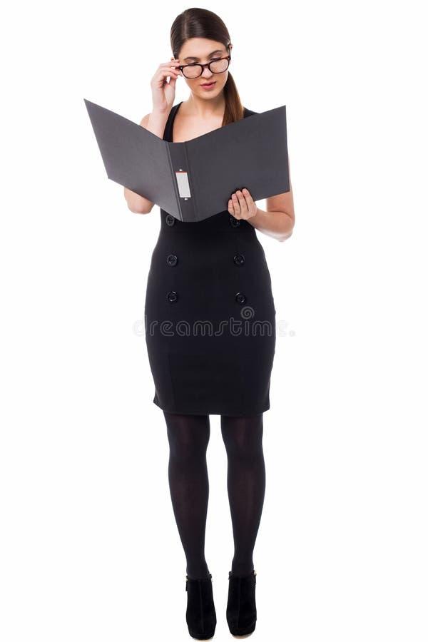 Mujer corporativa que revisa el documento anual fotos de archivo libres de regalías
