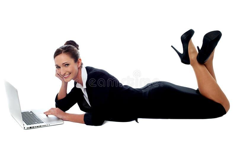 Mujer corporativa relajada que trabaja en el ordenador portátil imagen de archivo