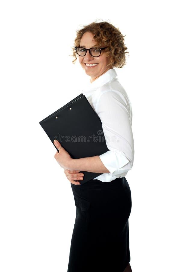 Mujer corporativa sonriente que presenta con el sujetapapeles fotos de archivo