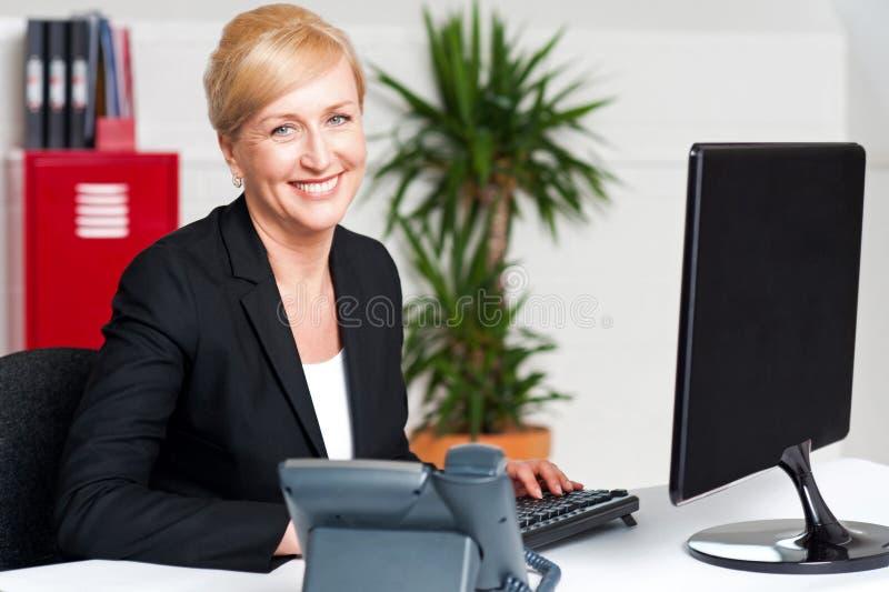Mujer corporativa sonriente que pulsa en el teclado imágenes de archivo libres de regalías