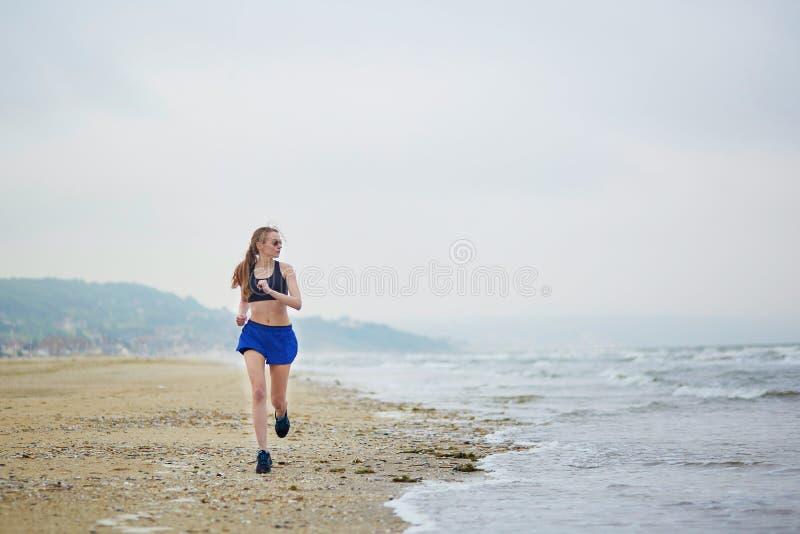 Mujer corriente de la aptitud joven que activa en la playa imagen de archivo