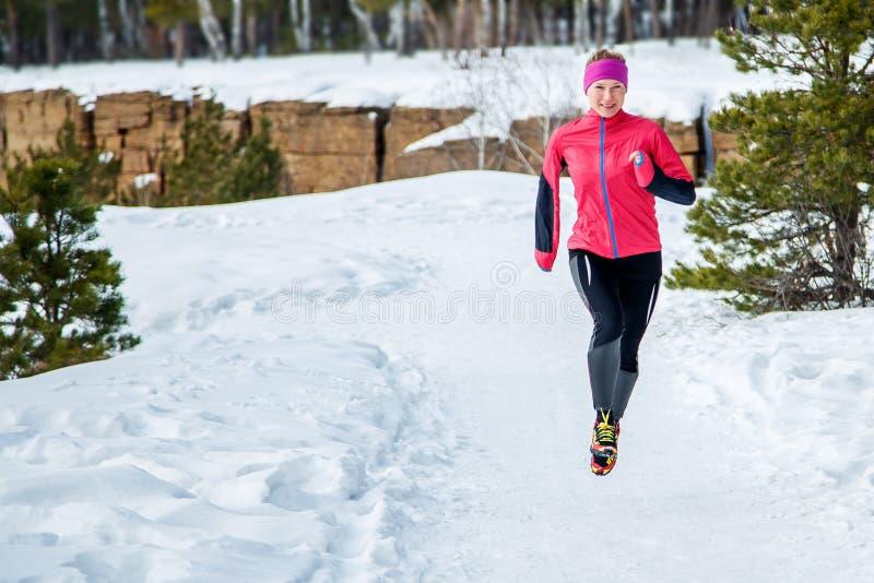 Mujer corriente del deporte Corredor femenino que activa en el bosque frío del invierno que lleva la ropa corriente deportiva cal imágenes de archivo libres de regalías