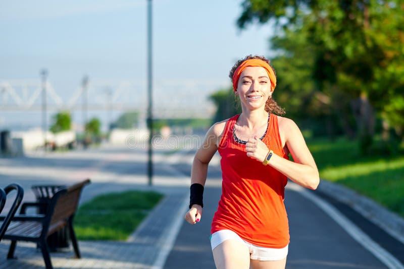 Mujer corriente en pista durante la sesi?n de formaci?n Corredor femenino que practica en circuito de carreras del atletismo imágenes de archivo libres de regalías
