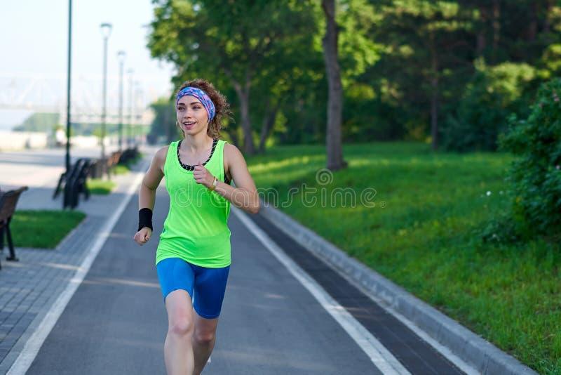 Mujer corriente en pista durante la sesi?n de formaci?n Corredor femenino que practica en circuito de carreras del atletismo fotografía de archivo