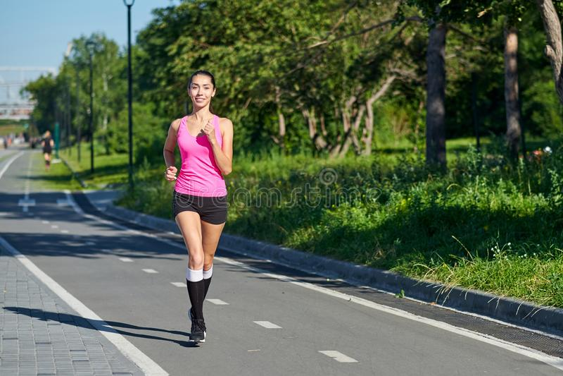 Mujer corriente en pista durante la sesi?n de formaci?n Corredor femenino que practica en circuito de carreras del atletismo fotos de archivo