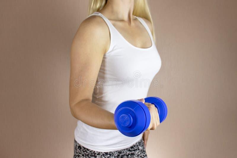 Mujer cosechada en la camisa blanca con el dambbell en su mano Adelgazar concepto de la dieta y de la aptitud imagenes de archivo
