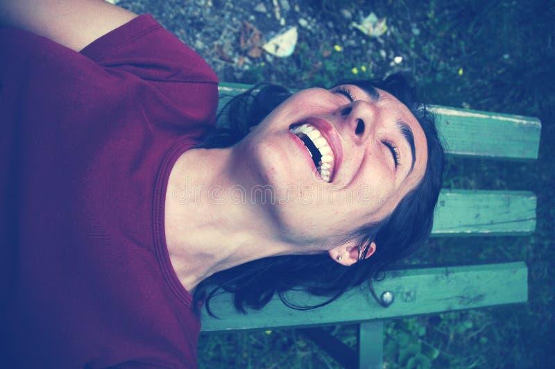 Mujer cosquilleada que ríe en un banco fotografía de archivo libre de regalías