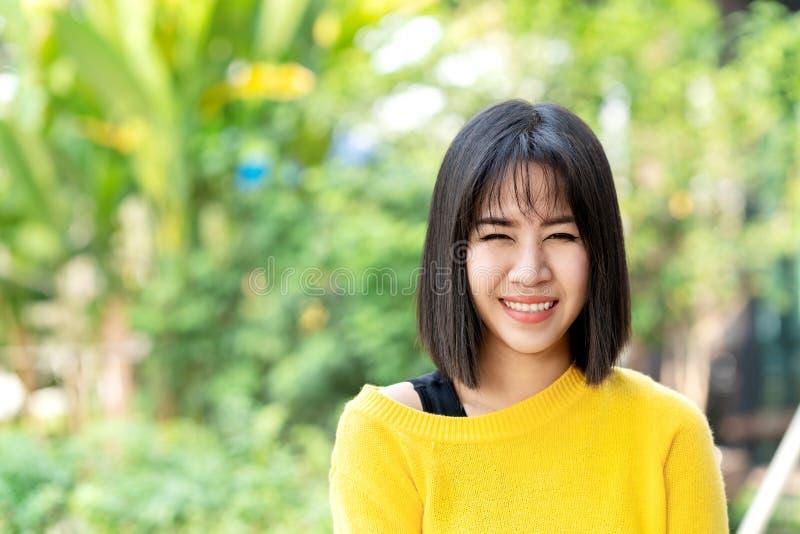 Mujer creativa del diseñador del asiático atractivo joven que se coloca, sonriendo, mirando la cámara que siente feliz y positiva imágenes de archivo libres de regalías