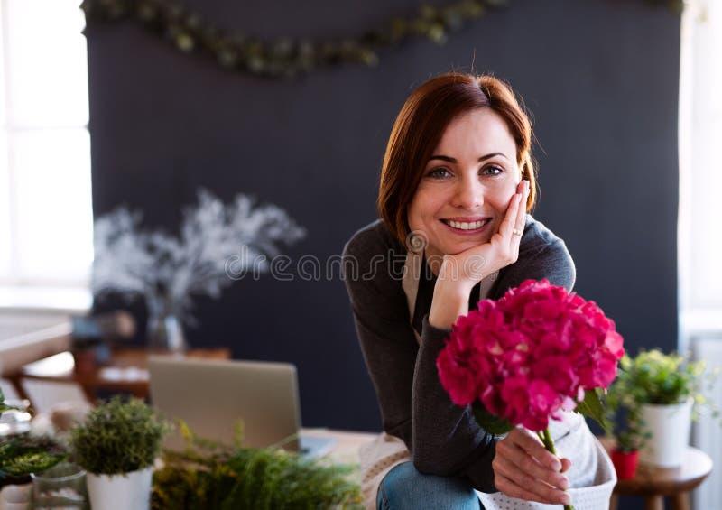 Mujer creativa joven en una floristería Un inicio del negocio del florista imágenes de archivo libres de regalías