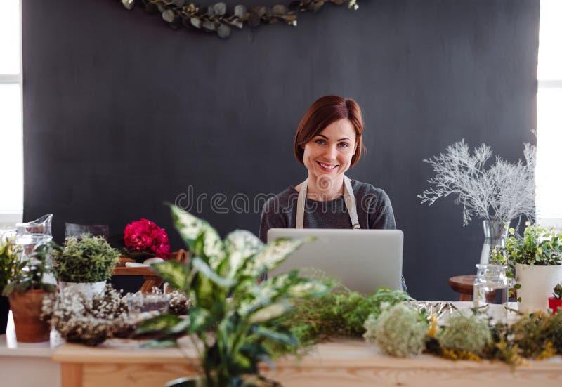 Mujer creativa joven en una florister?a, usando el ordenador port?til Un inicio del negocio del florista foto de archivo