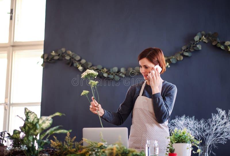 Mujer creativa joven en una florister?a, usando smartphone Un inicio del negocio del florista imagenes de archivo