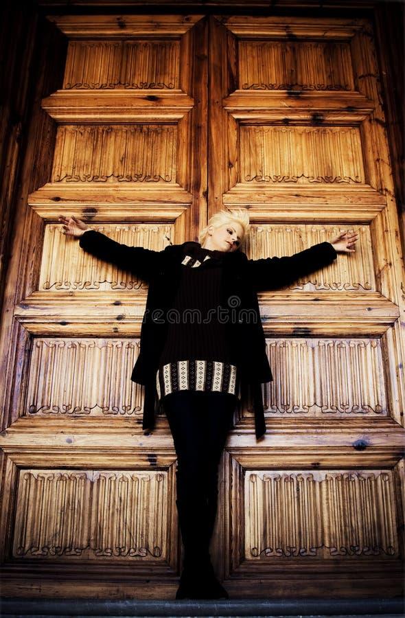 Mujer crucificada en puerta de madera de la iglesia fotos de archivo