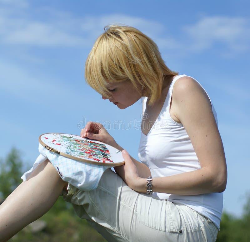 Mujer cruz-que cose en el parque imagen de archivo libre de regalías
