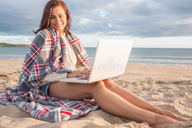 Mujer cubierta con la manta usando el ordenador portátil en la playa fotografía de archivo