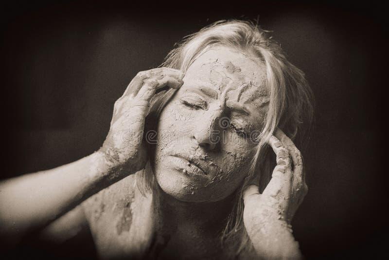 Mujer cubierta en la máscara agrietada seca de la arcilla que lleva a cabo su cabeza imagen de archivo libre de regalías