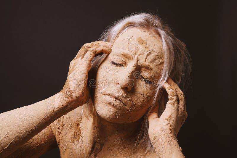 Mujer cubierta en la máscara agrietada seca del fango de la arcilla que lleva a cabo su cabeza fotografía de archivo