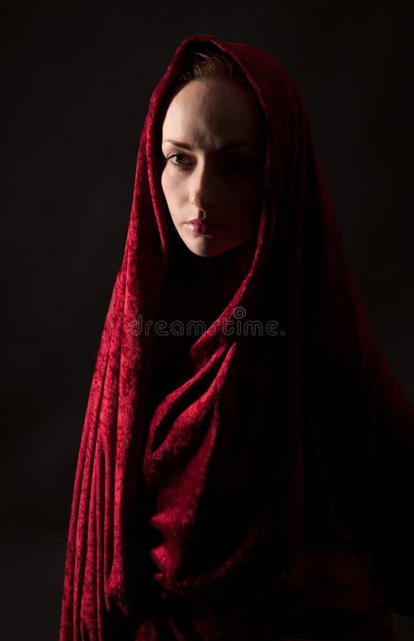 Mujer cubierta en tela roja del terciopelo fotografía de archivo libre de regalías