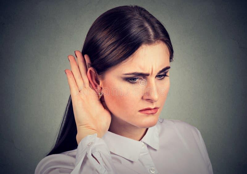 Mujer curiosa con la mano al oído que escucha cuidadosamente la conversación del chisme foto de archivo