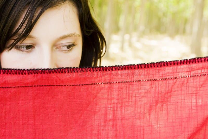 Mujer curiosa detrás del velo foto de archivo