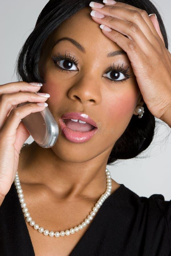 Mujer dada una sacudida eléctrica del teléfono foto de archivo