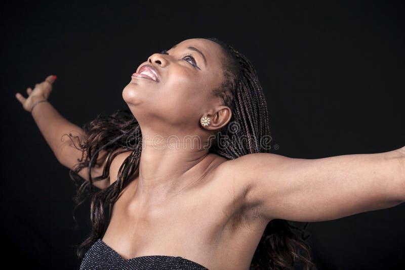 Mujer de Aframerican sobre un fondo negro imágenes de archivo libres de regalías