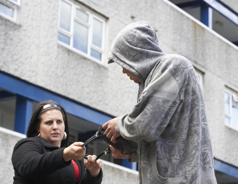 Mujer de agresión del hombre en calle imagen de archivo