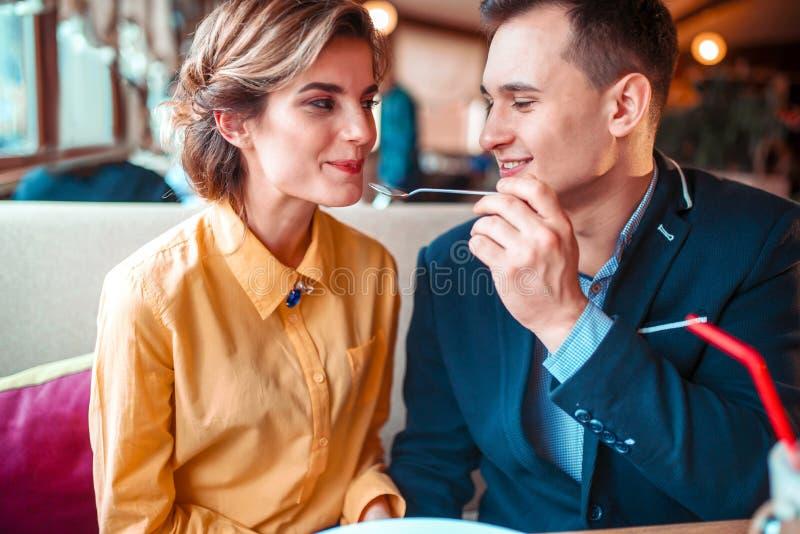 Mujer de alimentación sonriente del hombre con la cuchara en restaurante foto de archivo