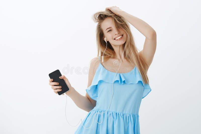 Mujer de amistoso-mirada sincera apacible y atractiva con el pelo rubio que juega con el peinado como el baile y salto fotografía de archivo