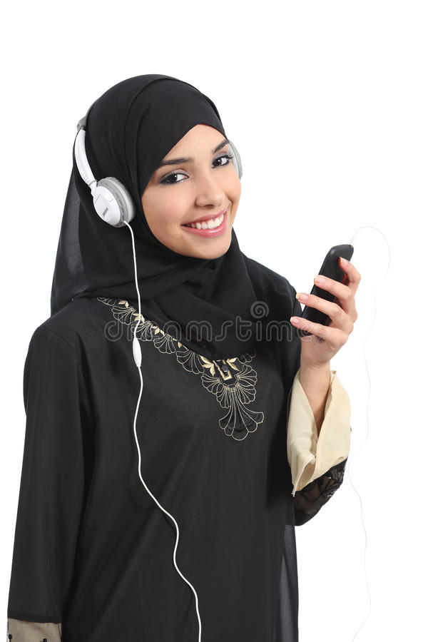 Mujer de Arabia Saudita que escucha la música de un teléfono elegante foto de archivo