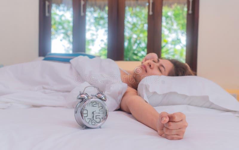 Mujer de Asia que miente en cama por la mañana Ella es intento que despierta con el despertador imagen de archivo libre de regalías