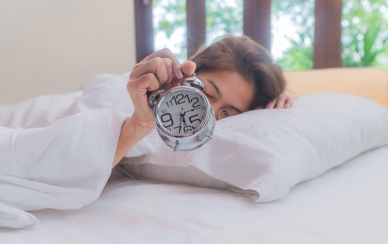 Mujer de Asia que miente en cama por la mañana Ella es intento que despierta con el despertador imagenes de archivo