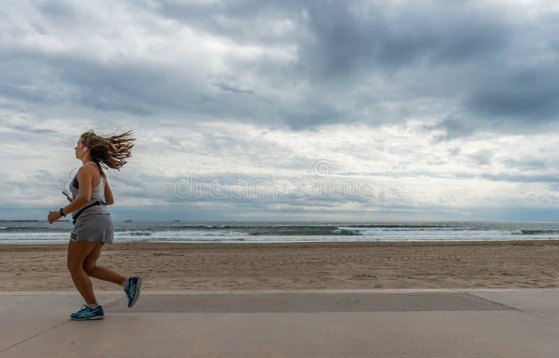 Mujer de Atlethic que corre delante de la playa fotografía de archivo libre de regalías
