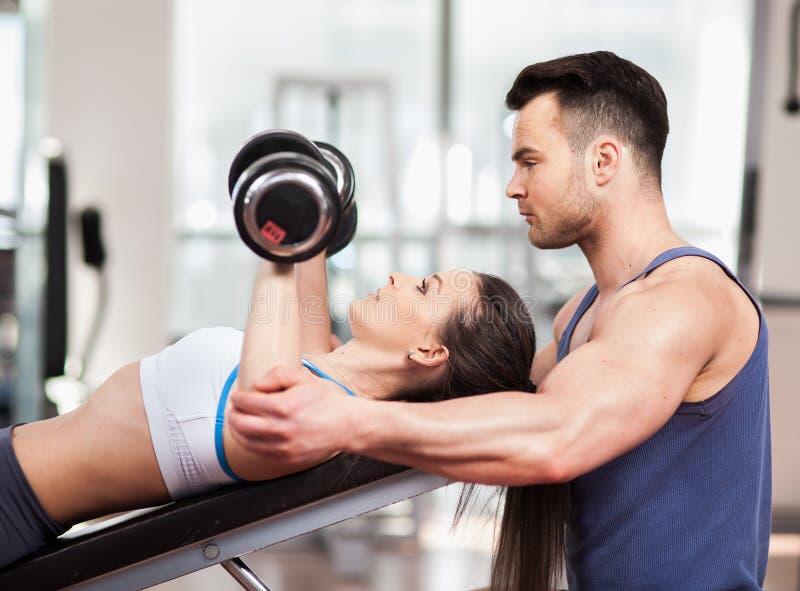 Mujer de ayuda del instructor personal que trabaja con pesas de gimnasia fotografía de archivo