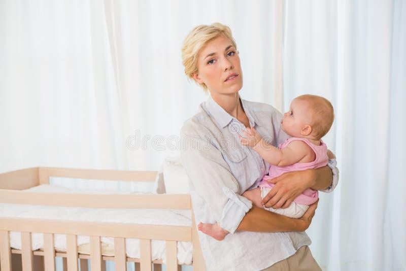 Mujer de Beauitiful que detiene a su bebé fotografía de archivo libre de regalías