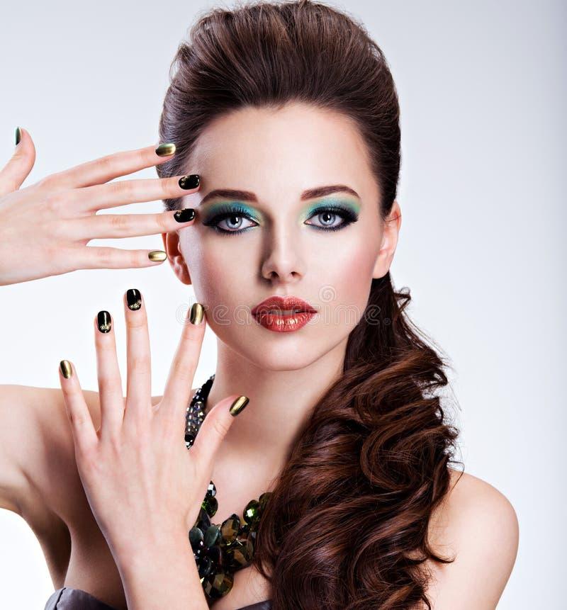 Mujer de Beautiul con maquillaje verde color creativo de clavos fotografía de archivo