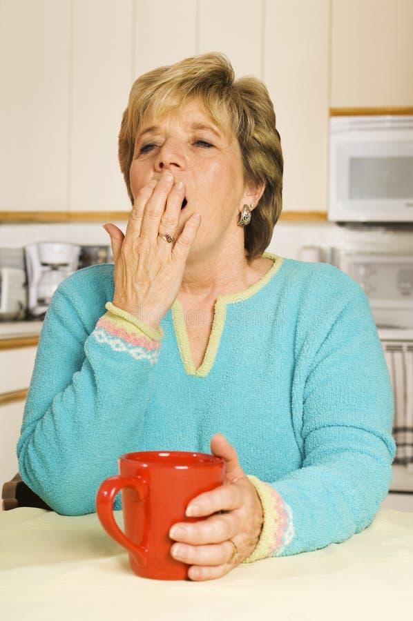 Mujer de bostezo con la taza de café roja en su cocina fotografía de archivo