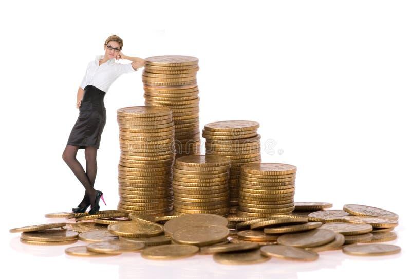 Mujer de Busines con las monedas de la columna imagen de archivo