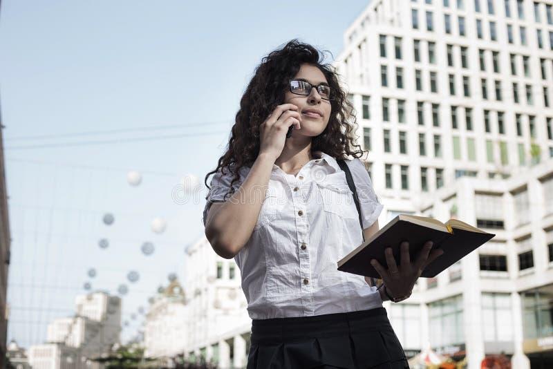 Mujer de Businnes en ropa del estilo de la oficina que habla en el teléfono móvil con el cliente y que sostiene a disposición su  fotografía de archivo