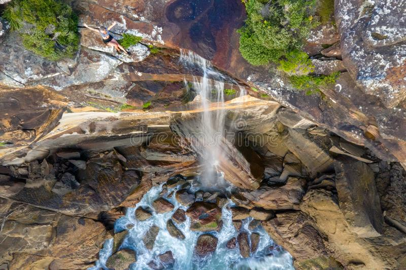 Mujer de Clifftop que se sienta por el borde de la cascada que cae en el océano foto de archivo