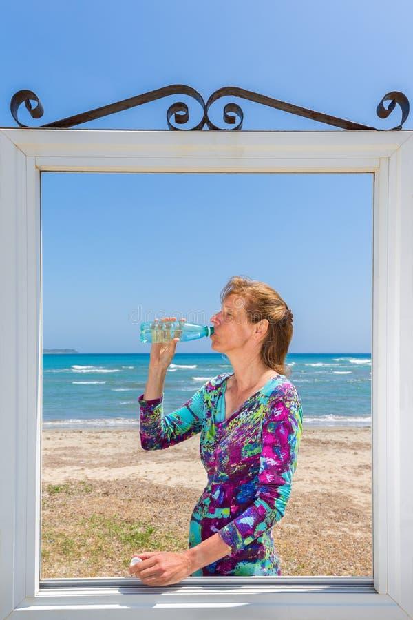 Mujer de consumición en ventana en el mar foto de archivo libre de regalías