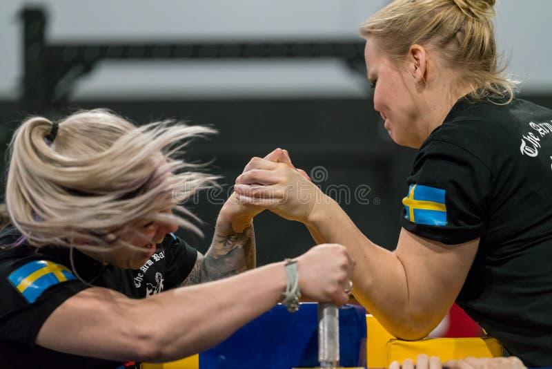 Mujer de dos suecos en una lucha dura del pulso imagen de archivo libre de regalías