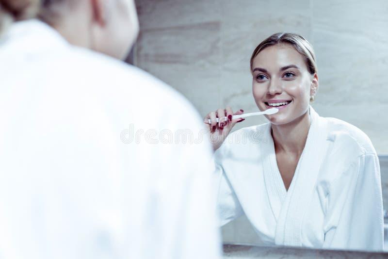 Mujer de emisión con el cepillo de dientes rojo de la tenencia del arte del clavo que cepilla sus dientes imagen de archivo libre de regalías