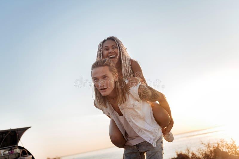 Mujer de emisión con los dreadlocks que sienten alegres divirtiéndose con el novio imagen de archivo libre de regalías