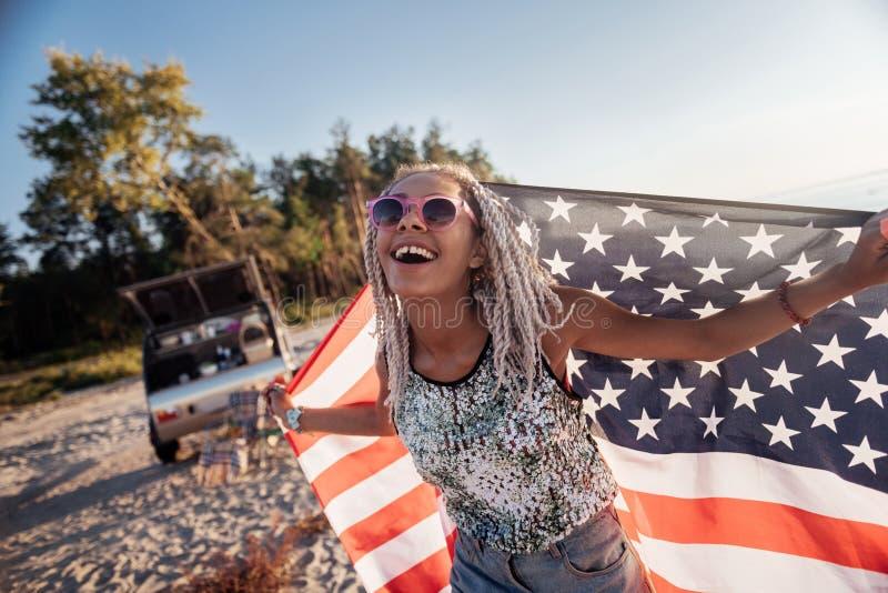 Mujer de emisión con los dreadlocks que sostienen la bandera de América mientras que viaja fotografía de archivo
