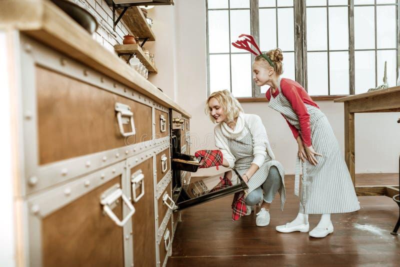 Mujer de emisión de pelo corto que usa el guante especial para poner la cacerola caliente fotografía de archivo libre de regalías