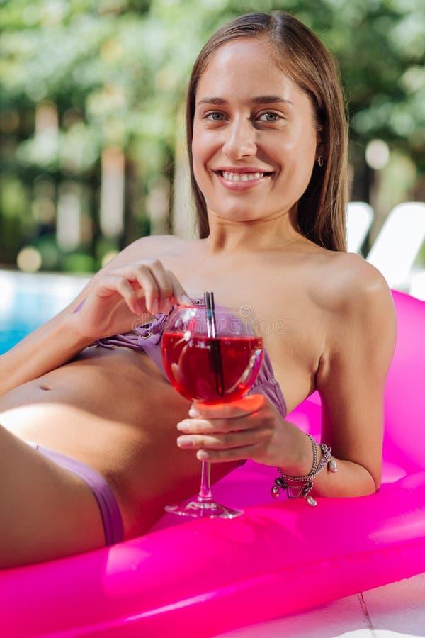 Mujer de emisión que miente en el colchón de aire en la piscina que lleva a cabo la bebida fría foto de archivo