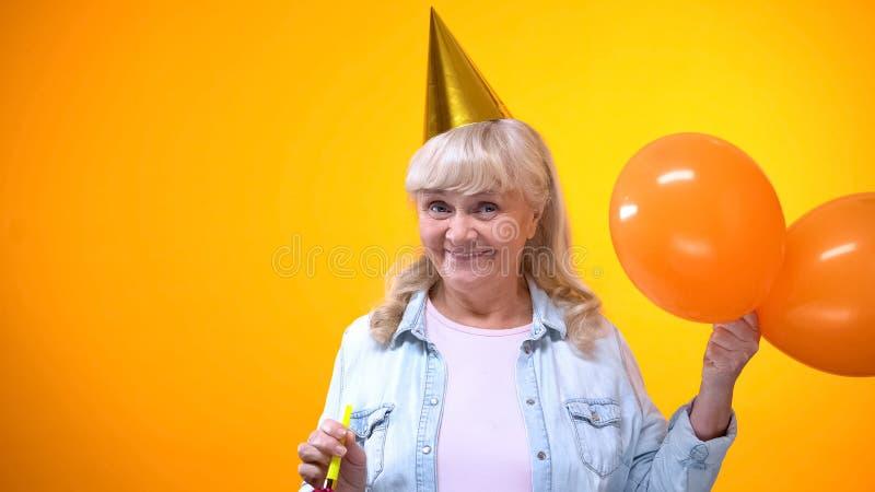 Mujer de envejecimiento alegre con los globos que celebra el cumpleaños, actitud positiva fotografía de archivo