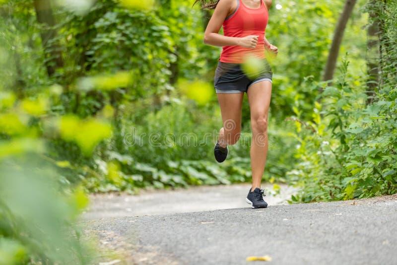 Mujer de funcionamiento del atleta en el primer que activa funcionado con de la trayectoria de los muslos de la parte inferior de imagenes de archivo