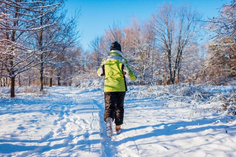Mujer de funcionamiento del atleta que esprinta en exterior del entrenamiento del bosque del invierno en tiempo nevoso frío fotos de archivo