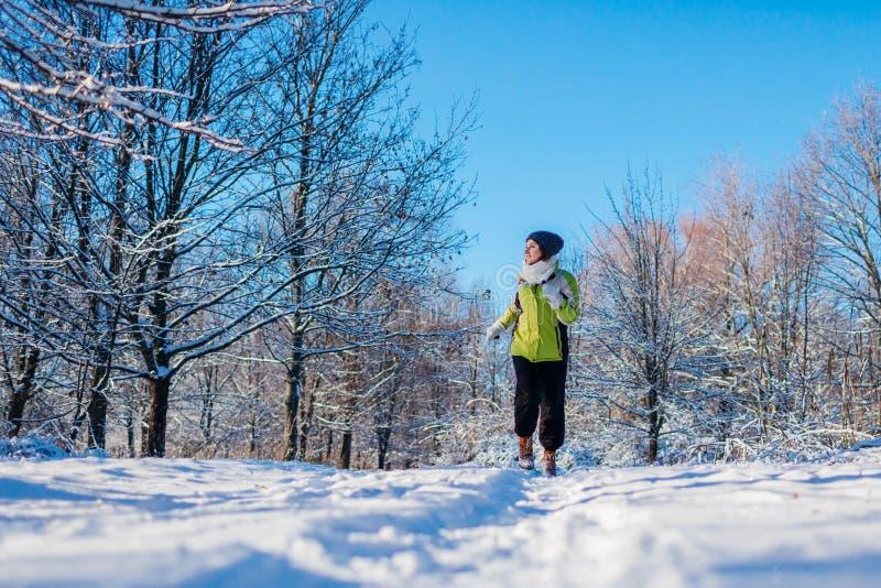 Mujer de funcionamiento del atleta que esprinta en exterior del entrenamiento del bosque del invierno en tiempo nevoso frío imagen de archivo